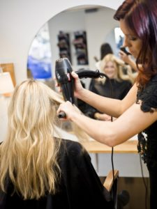 blonde woman getting hair done by cosmetologist